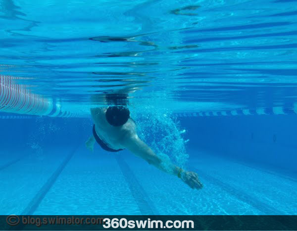 Keep one arm by the body and one arm swimming (not straight though)